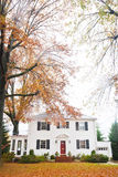 No Place Like Home. Large white brick home with black shutters and a red door. The lawn is covered with leaves. The vertical framing provides ample copy space stock image