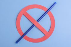 No plastic. Small blue straw in prohibition sign over a blue background, showing a sign of no plastic straw due to its effect on stock photography