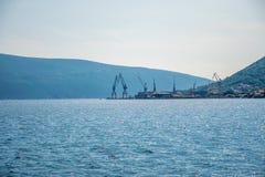 No porto há um descarregamento dos navios com grandes guindastes Imagens de Stock Royalty Free