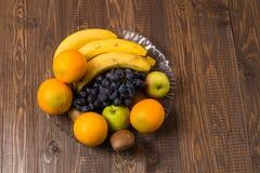 No prato são as bananas, as laranjas, as uvas e as maçãs heathful Imagem de Stock