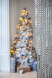 No primeiro plano a cortina é feita dos grânulos No fundo uma árvore de Natal borrada com brilho ilumina-se Fotografia de Stock Royalty Free