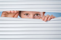No Privacy - Woman Peeking Through Blinds Royalty Free Stock Photos