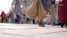 No quadro do pavimento europeu Os lotes dos pés, alguns povos na multidão levam malas de viagem vídeos de arquivo