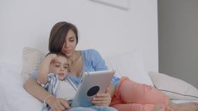 No quarto branco, olhar da mamã e do filho na tela e no riso da tabuleta Família feliz na cama na manhã que lê um livro vídeos de arquivo