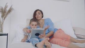 No quarto branco, olhar da mamã e do filho na tela e no riso da tabuleta Família feliz na cama na manhã que lê um livro video estoque