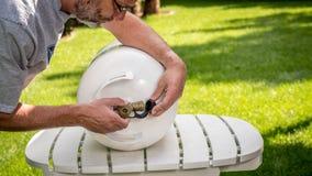 No quintal um homem substitui o tampão em uma garrafa do propano foto de stock