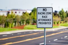 No racing zone sign on a post. With a street stock images