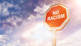 No racism, text on red traffic sign. No racism, text on red traffic stop sign in front of cloudy blue sky with lens flares Stock Photo