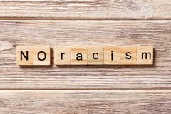 No racism word written on wood block. No racism text on table, concept.  Royalty Free Stock Photography