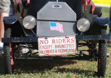 No Riders except brunettes, blondes and redheads. Small antique car with No riders except brunettes, blondes and redheads signage on the front license plate in a Royalty Free Stock Image