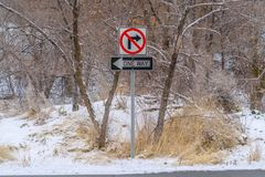 No Right Turn and One Way sign against snowy trees royalty free stock image