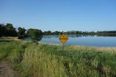 A no road maintenance sign beside a lake Stock Photo