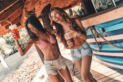 No rules for them. Two attractive young women smiling and enjoying cocktails while dancing near the bar counter royalty free stock photos