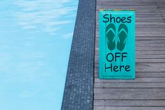 No shoes sign by the swimming pool on the wooden floor in green royalty free stock image