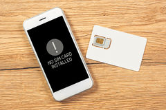 No SIM card installed notification on smartphone screen. Top view mock up for telecommunication provider microchip with mobile phone on office desktop Royalty Free Stock Image