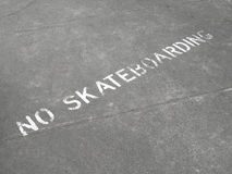 No Skateboarding sign painted on sidewalk. A sign painted on the sidewalk of a city, warning that skateboarding is prohibited royalty free stock image