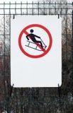 No sledding allowed sign. On green metallic fence Royalty Free Stock Photos