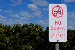 No sleeping in vehicles sign. An outdoors road sign reads: No sleeping in vehicles in the parking place royalty free stock photography