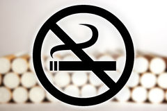 No Smoking. Black no smoking sign in front of a blurry picture of cigarettes Royalty Free Stock Photo