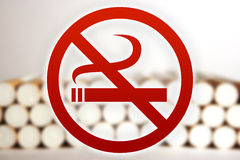 No Smoking. Red no smoking sign in front of a blurry picture of cigarettes Royalty Free Stock Images