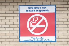 No Smoking On Hospital Grounds Property Sign On Brick Wall stock images