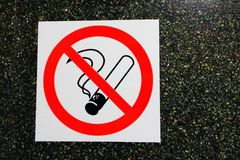 No smoking icon sticker on dark stone wall background stock photo