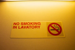 No smoking in lavatory sign warning in a toilet on airplane Royalty Free Stock Photos