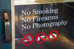 No Smoking, No Firearms, No Photography sign at the door  entrance Royalty Free Stock Photo