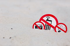 No smoking, No photo and No phone calls signs on the beach. On sand background Royalty Free Stock Photo
