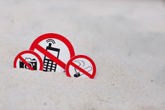 No smoking, No photo and No phone calls signs on the beach. On sand background Stock Photography