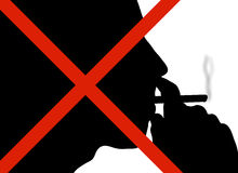 No Smoking Sign. Silhouette of man puffing on a cigarette with red cross over his face Stock Photography