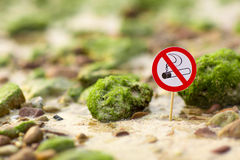No smoking sign on the beach. On seastones background Royalty Free Stock Photos