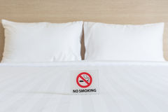 NO SMOKING Sign on the bed in hotel room Stock Image