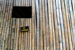 No smoking sign attached to old bamboo wall. stock image