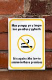 No Smoking Sign on a brick wall. No Smoking Sign, Yellow and white signage with the words It is against the law to smoke on these premises, Welsh and English Royalty Free Stock Photography