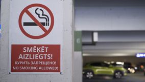 No smoking sign in English, Russian and Latvian at a shopping mall. Smooth camera slider movement and 80 percent slow motion stock footage
