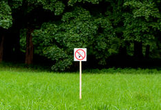 No smoking sign in the park on bright green trees and grass background. royalty free stock photo