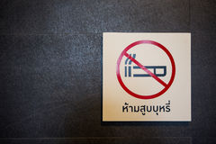 No smoking sign on the wall. No smoking sign on the black wall with thai language Royalty Free Stock Photography