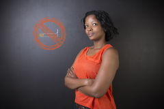 No smoking tobacco South African or African American woman on blackboard background. No smoking tobacco addict South African or African American woman teacher or Royalty Free Stock Photo