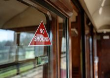No Smoking warning sign seen attached to a first-class railway compartment. stock photography