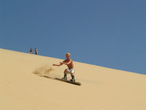 No snowboard, it's a sandboard. Sandboarding at the sand dune in Arcachon, France. It's the biggest sand dune of Europe and this sport is kind of new and unusual stock photo