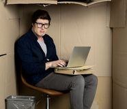 Young miserable manager is working in cramped cardboard room. No space concept. Portrait of depressed employee is sitting in cramped carton office and typing on royalty free stock photos