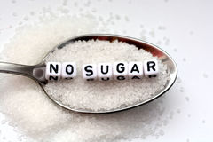 No sugar phrase made from plastic letter cubes placed in a spoon full of sugar. No sugar phrase formed with plastic letter cubes placed in a spoon full of sugar Stock Images