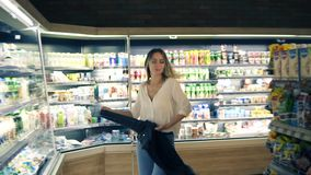 No supermercado: a jovem mulher feliz dança através dos bens e dos produtos láteos nas prateleiras Decole seu revestimento preto video estoque