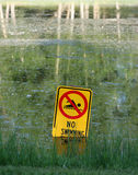 No swimming. Sign in small pond stock image