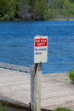 No Swimming Allowed Sign. A photo of a no swimming sign with water and trees in the background Stock Photos