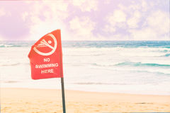No swimming danger sign at the beach, warning sign at the beach. With people swim, caution no swimming allowed stock image