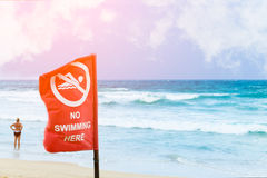 No swimming danger sign at the beach, warning sign at the beach. With people swim, caution no swimming allowed royalty free stock photo