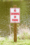 No swimming or Fishing sign on wooden post in national green par. K royalty free stock photo