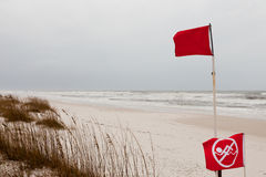No swimming flag on stormy ocean sand beach Royalty Free Stock Photos